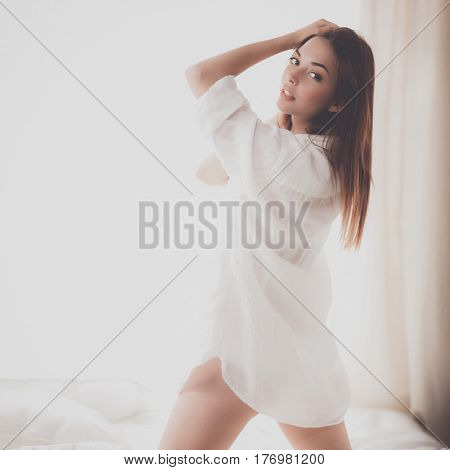 Portrait of beautiful woman on bed at bedroom