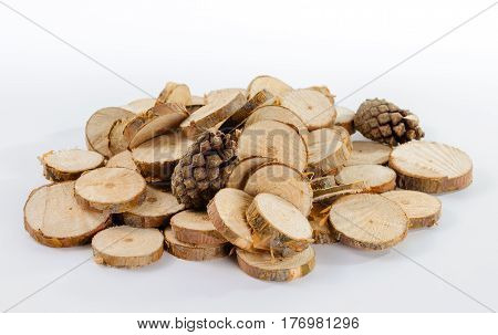 Pile of little round pieces of sawn pine branches and pine cones on white background