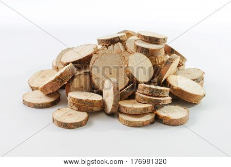 Stack of many little round pieces of sawn pine branches on white background