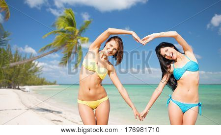 summer holidays, travel, people, love and vacation concept - happy young women in bikinis making heart shape with hands over exotic tropical beach with palm trees and sea shore background