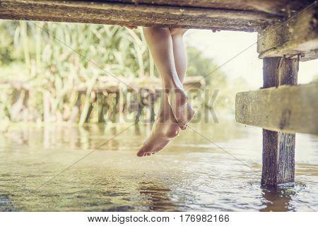 Female Legs Splashing In The Pool Of Water