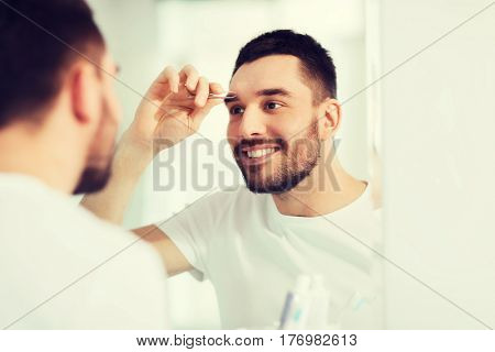 beauty and people concept - smiling young man with tweezers tweezing eyebrow and looking to mirror at home bathroom