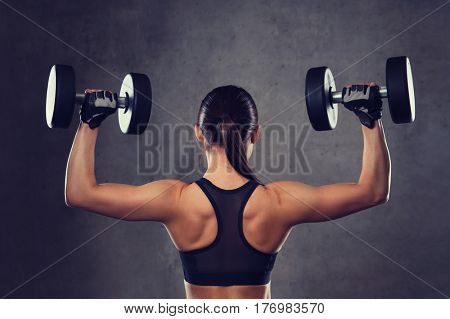 fitness, sport, exercising, training and people concept - young woman flexing muscles with dumbbells in gym poster