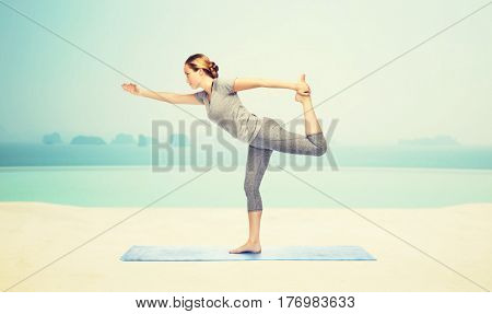 fitness, sport, people and healthy lifestyle concept - woman making yoga in lord of the dance pose on mat over infinity edge pool at hotel resort background