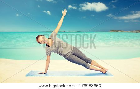fitness, sport, people and healthy lifestyle concept - woman making yoga in side plank pose on mat over sea and sky background