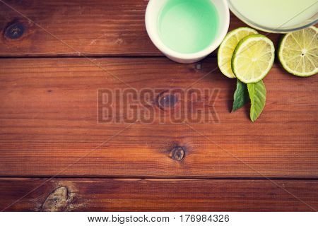 beauty, spa, body care and natural cosmetics concept - close up of bowls with citrus body lotion, cream and limes on wooden table