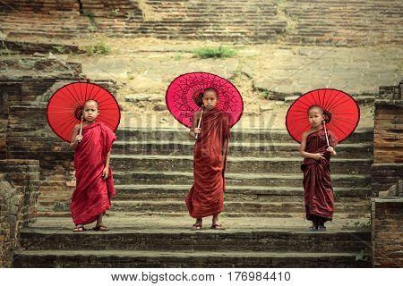 Myanmar The three novice walking on the Mingun pagoda and holding red umbrella in MandalayMyanmar.