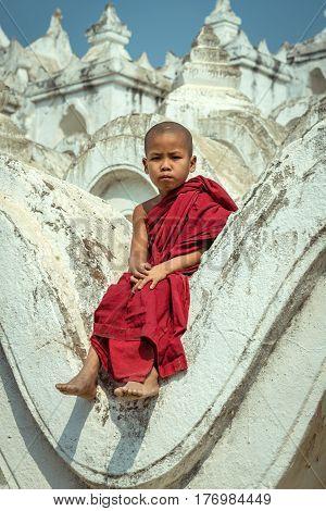 Myanmar novice sitting on the hsinbyume pagoda