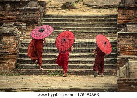 Myanmar The backside three novice walking on the Mingun pagoda and holding red umbrella in MandalayMyanmar.