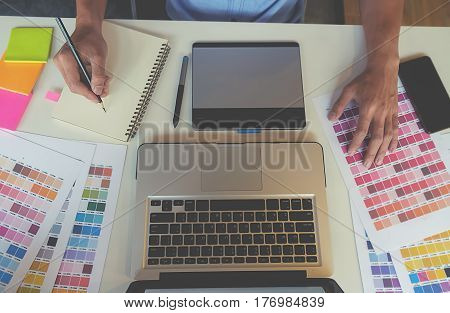 Graphic design and color swatches and pens on a desk. Architectural drawing with work tools and accessories.