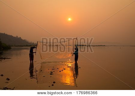 Thai fisherman silhouette in sunrise landscape Mekong river are catching fish together with friend. Is life's thai and Laos people's Fisherman of Mekong river asia.