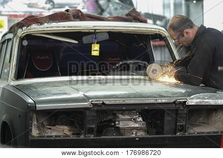 Kaluga, Russia - March, 16, 2017: Worker works with angle grinder in a car repair shop