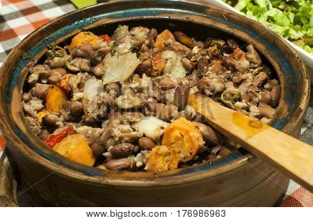Clay pot with boiled and baked beans with onions, carrots and spices