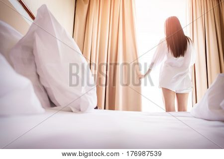 Healthy Woman Stretching In Bed Room And Open The Curtains After Wake Up, Back View, Lifestyle Peopl