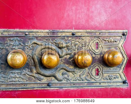 Beijing, China - Oct 30, 2016: Ornate brass gate plate design and patterns at the Forbidden City (Gu Gong, Palace Museum). Featuring studs and dynamic dragon artwork in relief.