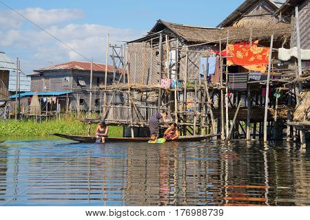 INLE LAKE, MYANMAR - DECEMBER 26, 2016: Women of the Intha people wash themselves in the lake near the house. Fishing village on Inle Lake Myanmar
