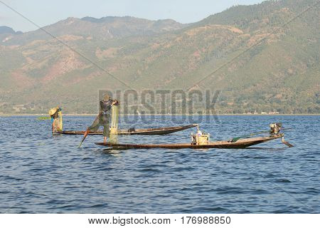 INLE LAKE, MYANMAR - DESEMBER 26, 2016: Two fishermen in traditional wooden boats to catch fish on the Inle lake