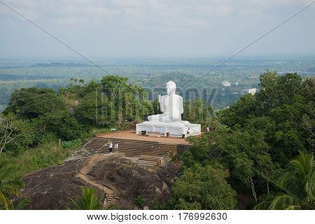 Sculpture of the sitting Buddha against the background of a cloudy landscape. The Mango Plateau in Mikhintale. Sri Lanka