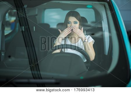 Beautiful Smiling woman driving car shocked with hands on mouth
