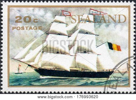 UKRAINE - CIRCA 2017: A stamp printed by Sealand showsTwo-masted sailing ship under the flag of the Kingdom of Belgium floating on the sea circa 1970