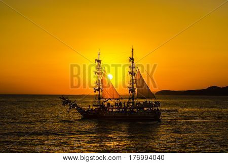 Silhouette two-masted sailing ship and of persons on Board on the background of orange sunset in the Mediterranean sea