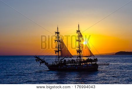 Two-masted sailing ship on the background of the setting sun.