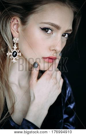 Portrait of the beautiful young woman with long brown hair posing at studio over dark background