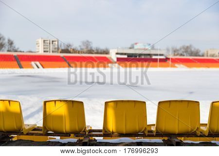 chairs at stadium , covered with snow in winter,