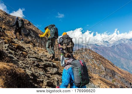 Group of People walking up on steep Mountain Trail using Hiking Gear carrying Backpacks