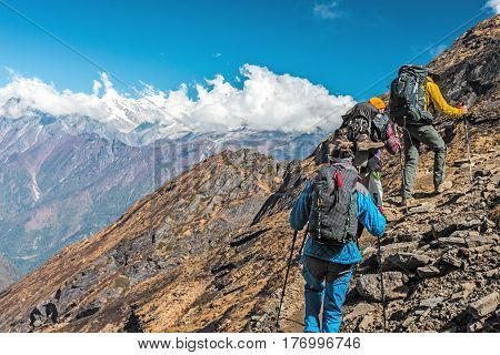 People travelling in Mountains walking up on steep rocky Path back View unrecognisable faces and copy space on left