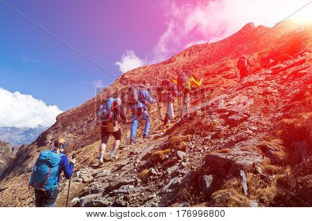 Mixed Group of Athletes mail and female young and mature walking up on steep mountain trail with backpacks and trekking poles bright Sun shining from Top.