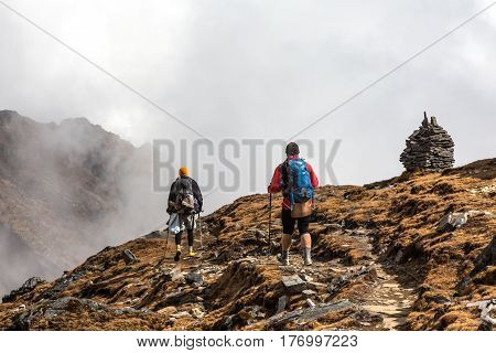 Two Hikers walking on Mountain Slope towards stone Towers. Heavy Fog arising from Valley on Background