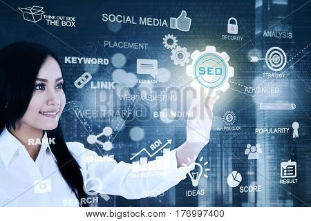 Photo of a young Asian businesswoman pressing a virtual SEO button on the futuristic screen. SEO concept
