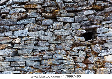Stone Wall of rural Building made with manual work without linking solution of small pieces of rocks carefully tailored to each other