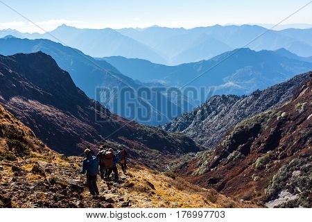 Group of People walking on Trek carrying Backpacks using trekking Sticks dressed in alpine Jackets and hiking Pants. Layered Mountains View beside