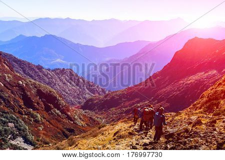 Group of People walking on Trek carrying Backpacks using trekking Sticks dressed in alpine Jackets and hiking Pants. Layered Mountains View with shining Sun beside