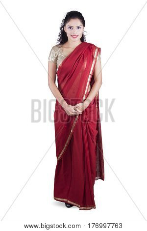 Full length of attractive Indian woman smiling at the camera while wearing a red saree clothes in the studio