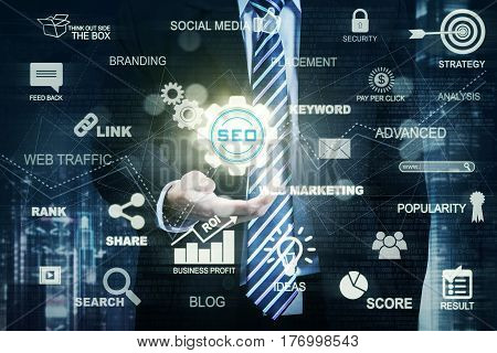 Picture of a businessman hand holding a virtual SEO icon while wearing formal suit. SEO concept