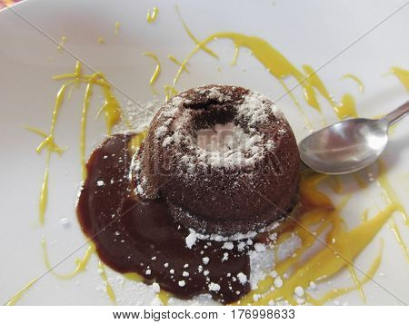 Warm chocolate fondant lava cake dessert with sweet zafferano sauce