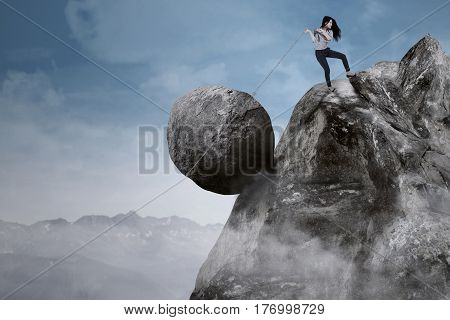 Young businesswoman is pulling big rock with a chain while climbing on the mountain