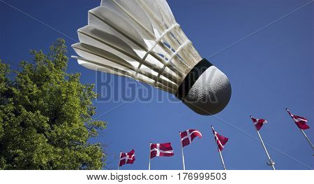 Danish Flags Blowing in the Wind and sky blue badminton shuttlecock.