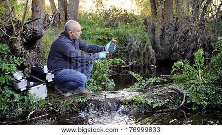 Biologist that collects data on temperature of a water course for the analysis of its pollution and for the study of its features.