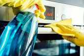 Man's hand in yellow rubber glove with rag cleaning kitchen oven poster