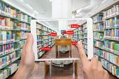 Augmented reality education concept. Hand holding digital tablet smart phone use AR application to check library category in bookshelf at university library. poster