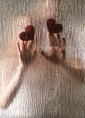 Hands of young couple with hearts behind riffled glass poster