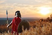 Incognito warrior in iron helmet and red cloak holding sword and looking at horizon. Male like spartan or antique roman with iron weapon before the battle. Sunset in field. poster