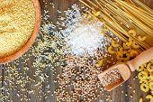 Gluten free cereals corn rice buckwheat quinoa millet and pasta on brown wooden backgroundoverhead horizontal view poster