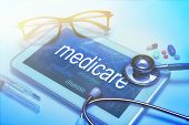Medicare word on tablet screen with medical equipment on background poster