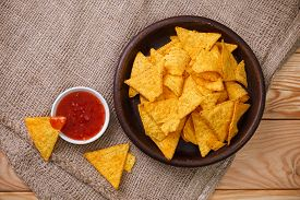 Nachos chips. Delicious salty tortilla with sweet salsa or chilli sauce on sackcloth background. Snack on rustic plate.