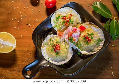 Baked Scallops With Garlic In A Black Pan